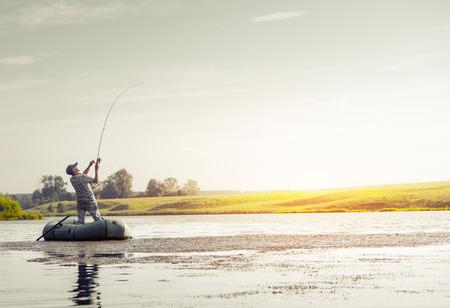 hombre pescando: pesca del hombre maduro en el lago desde el barco inflable Foto de archivo