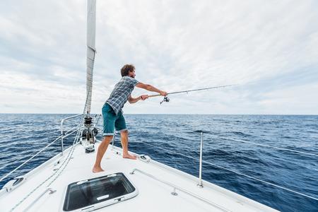 barca da pesca: Giovane uomo di pesca in mare aperto da barca a vela