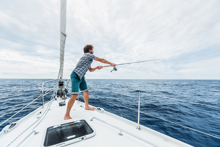 sea fishing: Young man fishing in open sea from sail boat