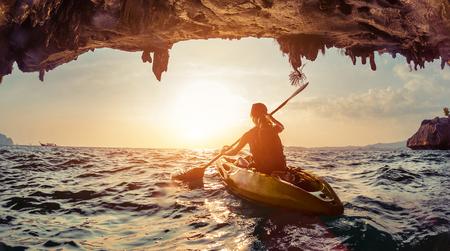 Señora remar el kayak en el mar agitado al atardecer.