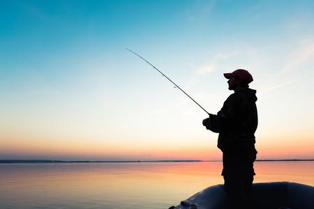 pesca: El hombre pesca desde el barco en el lago al atardecer Foto de archivo