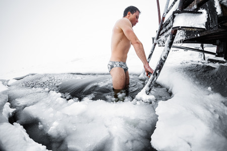 plunge: Young man swimming in the ice hole on a winter lake Stock Photo