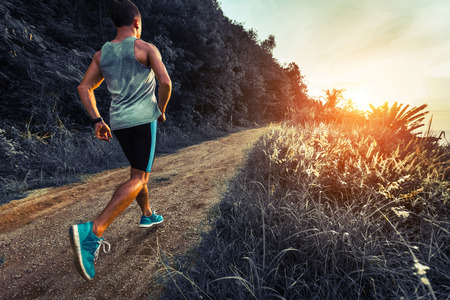 Man athlete running on the gravel road with green grass and trees on its sides