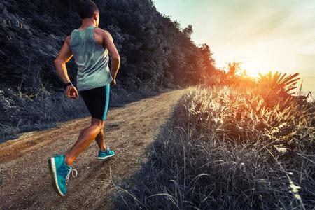 hombre deportista: Hombre atleta que se ejecuta en el camino de grava con la hierba verde y los árboles en sus lados Foto de archivo