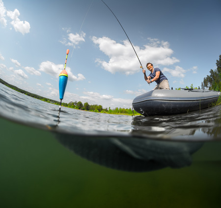 cyprinidae: Split shot of the man fishing on the lake with underwater view of the fish