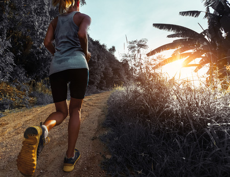 wet t shirt: Young woman jogging on the gravel road at sunset Stock Photo