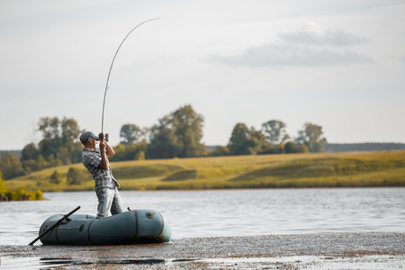 inflatable boat: Mature man fishing on the lake from inflatable boat