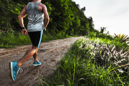 wet men: Man athlete running on the gravel road with green grass and trees on its sides