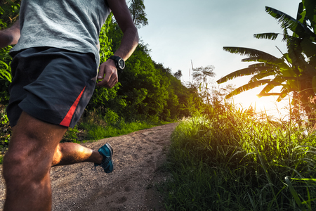 perspiration: Man jogging on the gravel road at sunset Stock Photo