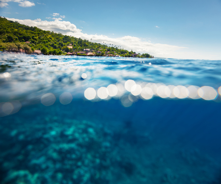 ocean water: Split shot with hilly tropical terrain on the surface and reef underwater