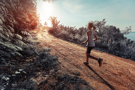 wet t shirt: Young woman running on the gravel road at sunset