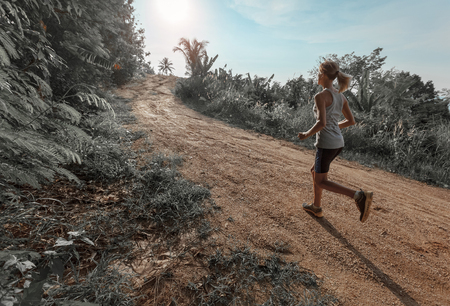 wet t shirt: Young woman jogging on the gravel road Stock Photo