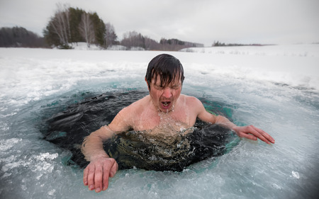 frozen lake: Young man swimming in the winter lake in the ice hole Stock Photo