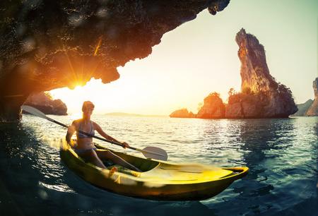 ocean kayak: se�ora joven que bate el kayak en una bah�a con las monta�as de piedra caliza. Foto de archivo