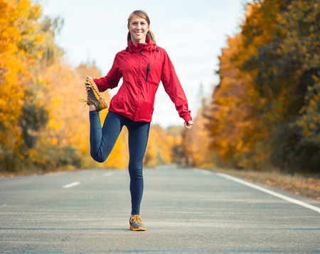 woman alone: Woman warms up and stretches on an asphalt road in an autumn forest Stock Photo