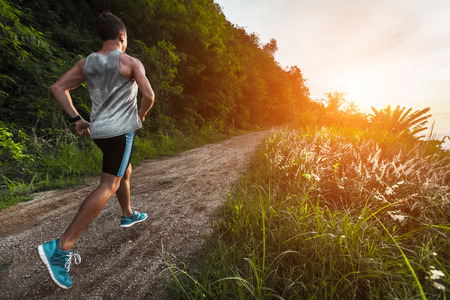 Man jogging on the gravel road at sunset Stock Photo