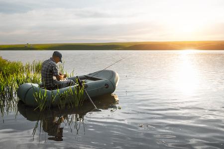 Homme qui pêche d'âge mûr sur le lac de bateau pneumatique Banque d'images - 54794951