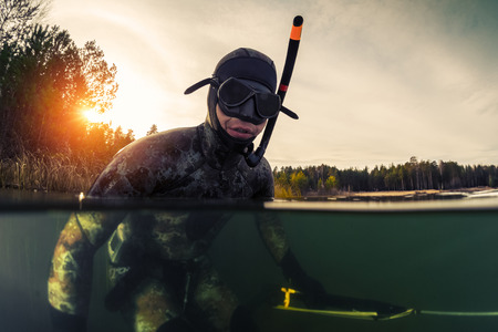 wet suit: Underwater split shot of the fisherman in wet suit and with a speargun Stock Photo