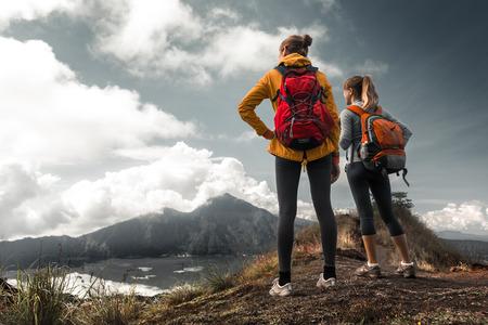 mochila de viaje: Dos excursionistas señoras de pie en la cima de la montaña y disfruta de la opinión del valle