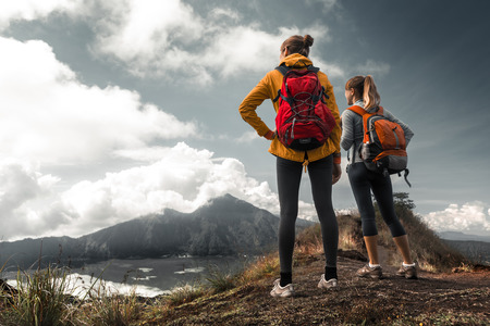 top mountain: Two ladies hikers standing on top of the mountain and enjoying valley view Stock Photo