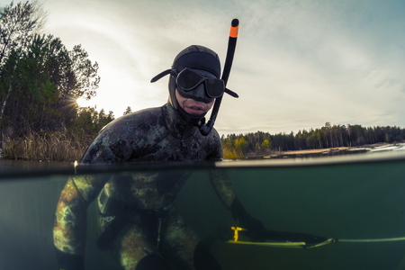 speargun: Underwater split shot of the fisherman in wet suit and with a speargun Stock Photo