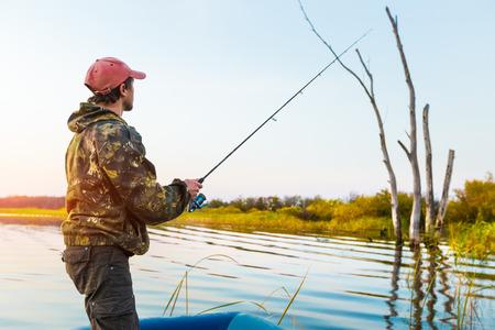 coger: El hombre pesca desde el barco en el lago al atardecer Foto de archivo