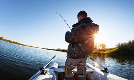 coger: El hombre pesca desde el barco en el lago del otoño
