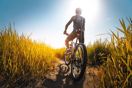 Młody sportowiec stojącego z rowerem na łące z żółtym bujnej trawie