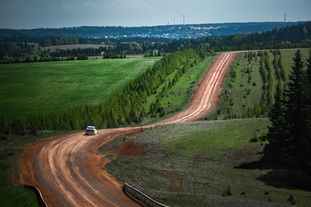unpaved road: Car moving on the unpaved road on hilly summer terrain