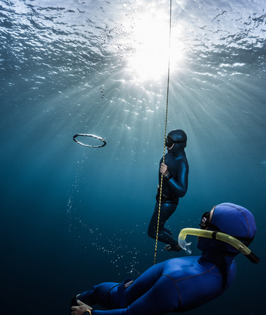 freediver: Couple of free divers having fun underwater, making ring bubbles Stock Photo