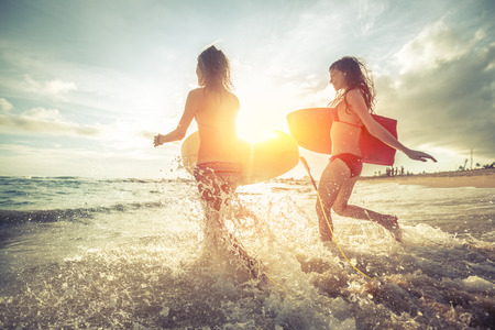 Two young women running into the sea with surf boards Foto de archivo
