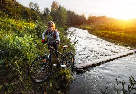 off road biking: Lady with bicycle crossing the river at sunset