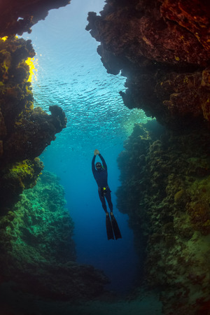 freediver: Free diver gliding in the cave of tropical sea Stock Photo