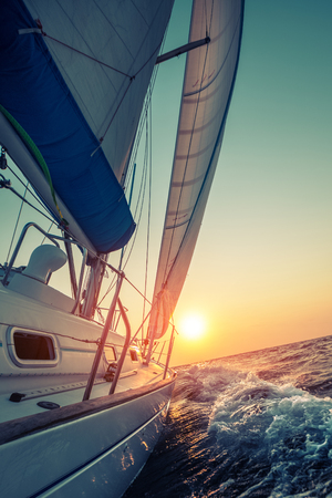 sail boat: Sail boat moving in the open sea at sunset Stock Photo