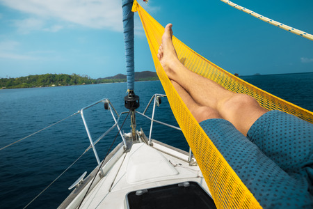 Man relaxing in the hammock set on the sail boat while it anchored near a shore