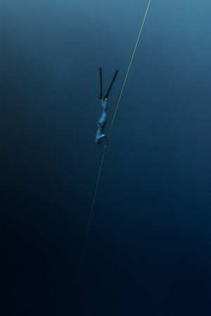 Free diver descending along the rope in the depth Stock Photo