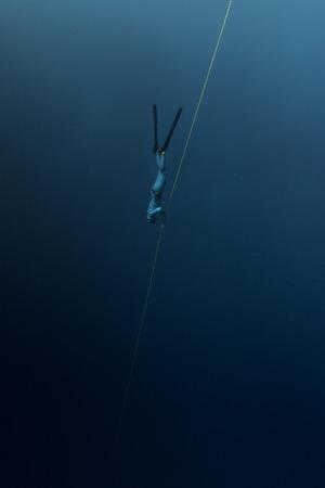 tiefe: Freier Taucher auf dem Seil in die Tiefe absteigend