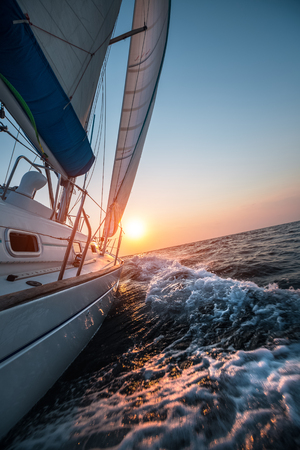 Sail boat moving in the open sea at sunset Stock Photo