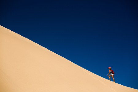 extreme sports: Hiker climbing the dune in the desert