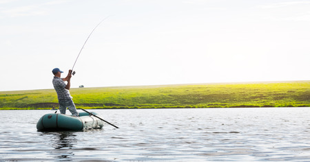 boats: Mature man fishing on the lake from inflatable boat
