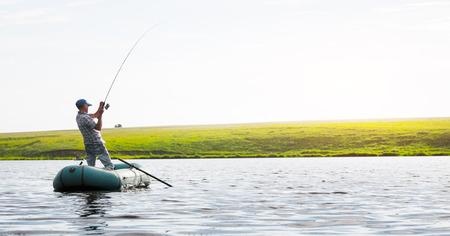 pesca: pesca del hombre maduro en el lago desde el barco inflable Foto de archivo