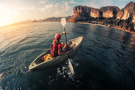 paddling: Woman paddling the sea kayak in the tropical calm lagoon with mountains