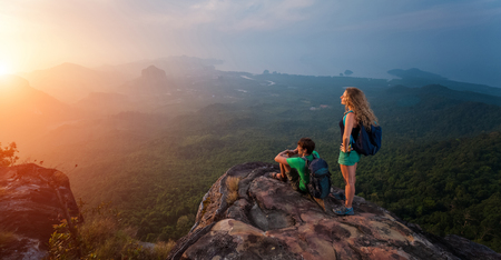 mountain sunset: Young man and woman standing on mountain at sunset Stock Photo