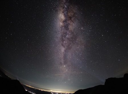latitude: Part of a night sky with stars and Milky Way on equatorial latitude with green tropical trees below Stock Photo