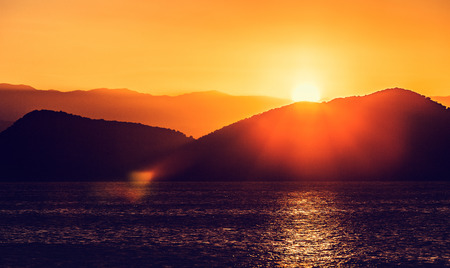 cliff edge: Sunset over a sea and mountains Stock Photo