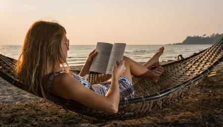 Señora joven que lee un libro en una hamaca en una playa al atardecer Foto de archivo