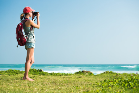 travel woman: Young lady with rucksack taking a picture of the sea standing on the green glage