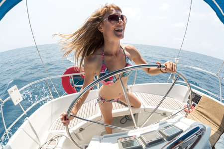 helm boat: Señora joven en el timón de un yate en el mar abierto Foto de archivo