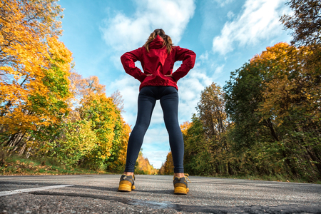 Lady in a track suit standing on the road in the woods
