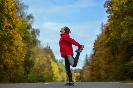 warms: Man warms up and stretches on an asphalt road in an autumn forest Stock Photo